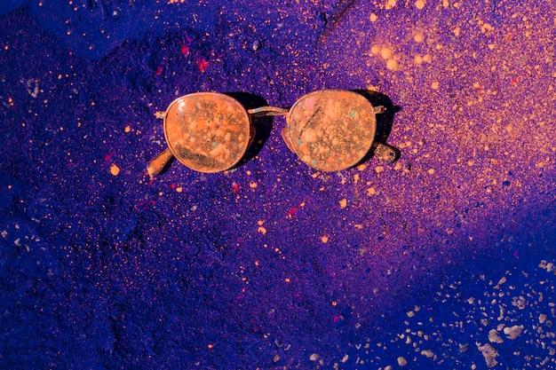 Eine orange holifarbe über der sonnenbrille auf blauem puder