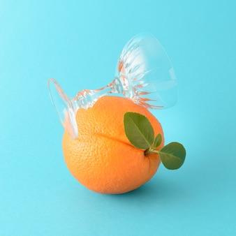 Eine orange mit grünem blatt und darauf steht ein schiefes glas auf blauem grund. fruchtiges konzept für zitrussaft, erfrischende sommertage und genuss.
