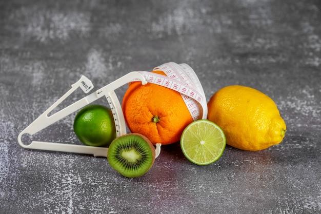 Eine orange, umwickelt mit einem maßband und einem messschieber, umgeben von frischen früchten. das konzept des abnehmens, cellulite entfernen, die figur in form bringen.