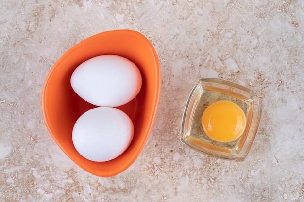 Eine orangenschale mit frischen weißen hühnereiern