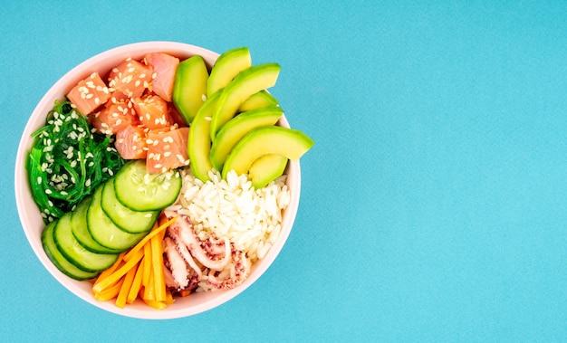 Eine overhead-poke-bowl, roher fischsalat aus algen, reis, lachs, gurke, sojasauce, avocado und sesam.