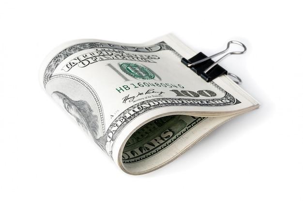 Eine packung amerikanischer hundertdollarscheine zur hälfte gefaltet und mit einem klerusverschluss befestigt.