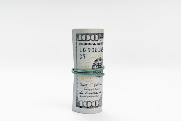Eine packung dollar mit einem gummiband auf weißem hintergrund gebunden. das konzept, geld in einer bank zu investieren und aufzubewahren. finanzkompetenz. tauschrate.