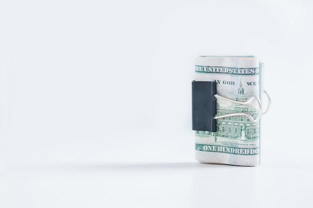 Eine packung mit hundert-dollar-scheinen liegt auf einem weißen tisch, der mit einer büroklammer befestigt ist. das konzept des sparens während der krise