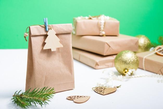 Eine packung öko-papier, verziert mit einem hölzernen weihnachtsbaum auf einer wäscheklammer, im hintergrund ein stapel geschenkboxen und goldene weihnachtskugeln, holzherzen, grüner hintergrund