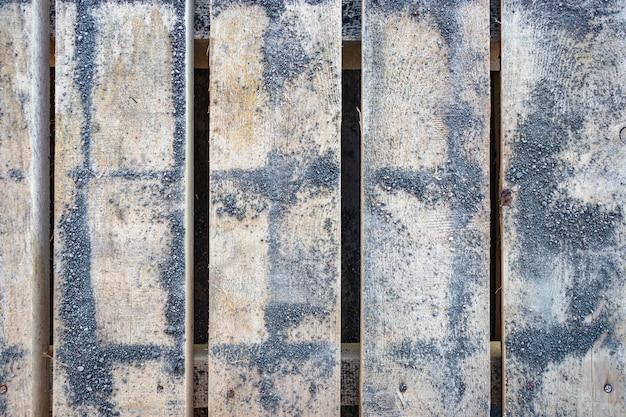Eine palette aus pflastersteinen, die mit betonspänen bedeckt sind. hintergrund von holzbohlen mit feinen betonspäne.