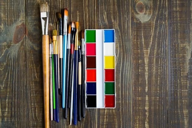 Eine palette der aquarellfarbe und des pinsels für das malen auf dunklem holztisch mit kopienraum. flach liegen.