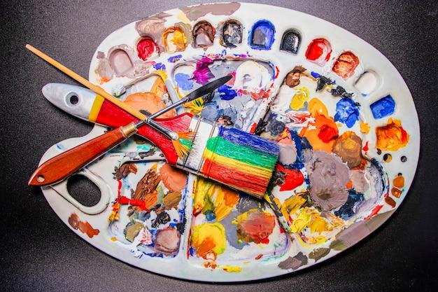 Eine palette mehrfarbiger farben mit pinseln und einem spachtel. schwarzer hintergrund. kreativität und zeichnen. offset-farben.