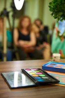 Eine palette von hellen schatten für make-up auf dem unscharfen hintergrund.