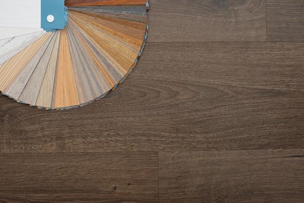 Eine palette von texturen und dekorationen für den holzboden aus laminat und vinyl auf einem dunklen holztisch. innenarchitektur. haus planen und bauen.