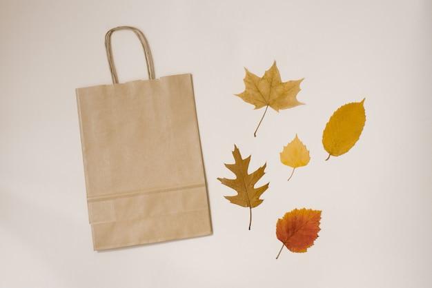 Eine papierhandwerkstasche mit einkaufsgriffen und herbst gefallenen blättern gelb und rot auf beigem hintergrund. herbstrabatte, preisverfall, schwarzer freitag, verkauf