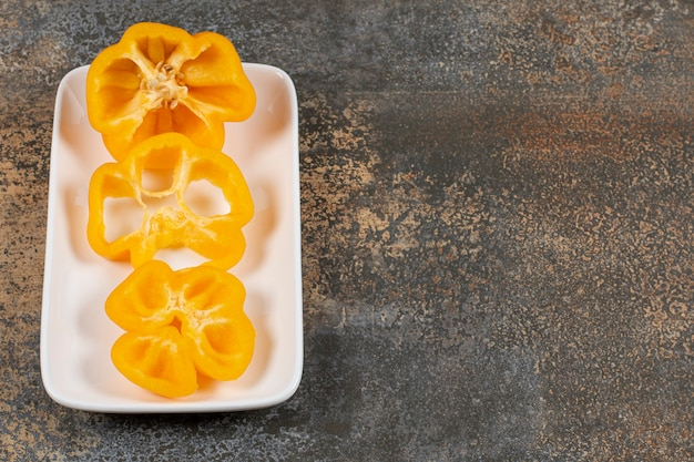 Eine paprika in scheiben auf dem teller auf der marmoroberfläche