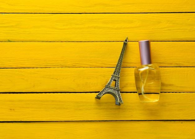 Eine parfümflasche und eine andenkenstatuette des eiffelturms auf einem gelben hölzernen hintergrund.