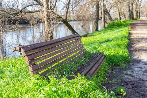 Eine parkbank ist menschenleer, während die natur ihren platz beansprucht und die vegetation durchwächst