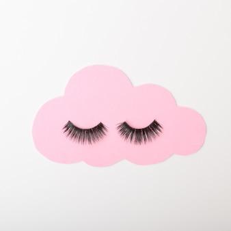Eine pastellrosa wolke mit schwarzen wimpern auf weißem hintergrund. cloud verbinden stillleben-inspiration. flacher rahmen.