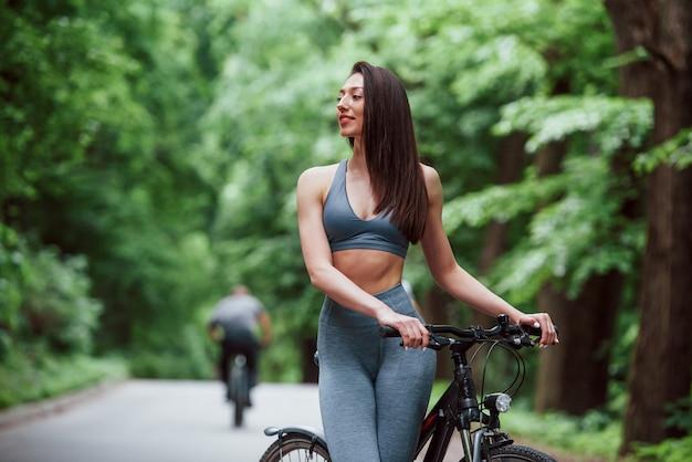 Eine pause machen. weiblicher radfahrer, der mit fahrrad auf asphaltstraße im wald am tag steht