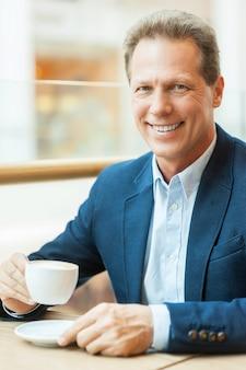 Eine pause mit frischem kaffee. fröhlicher reifer mann in abendkleidung, der kaffee trinkt und lächelt, während er im café sitzt?