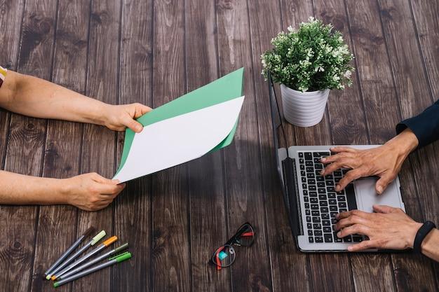 Eine person, die auf laptop mit seinem kollegen schreibt leeres weißes und grünes leeres papier auf holztisch schreibt
