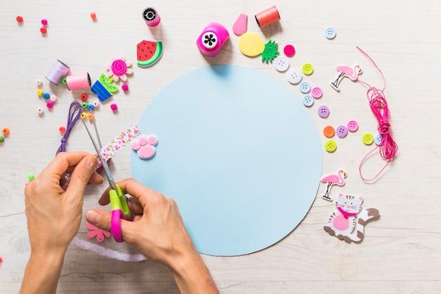 Eine person, die band mit scissor über dem blauen papier mit dekorativen elementen schneidet