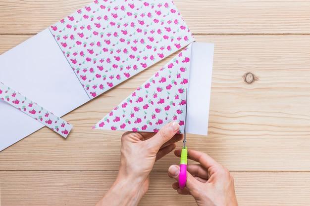 Eine person, die blumenpapier mit scissor über der tabelle schneidet