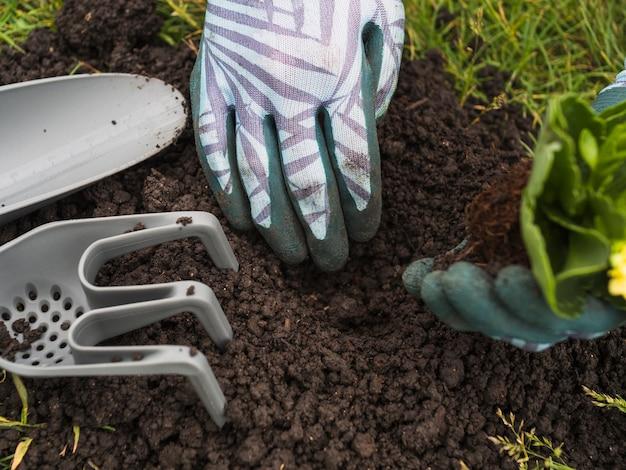 Eine person, die boden für das pflanzen von sämlingen gräbt