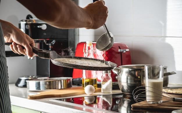 Eine person, die den teig in eine heiße pfanne gießt und köstliche hausgemachte pfannkuchen brät