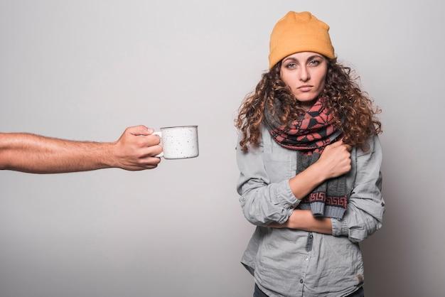 Eine person, die der kranken frau kaffee gegen grauen hintergrund gibt