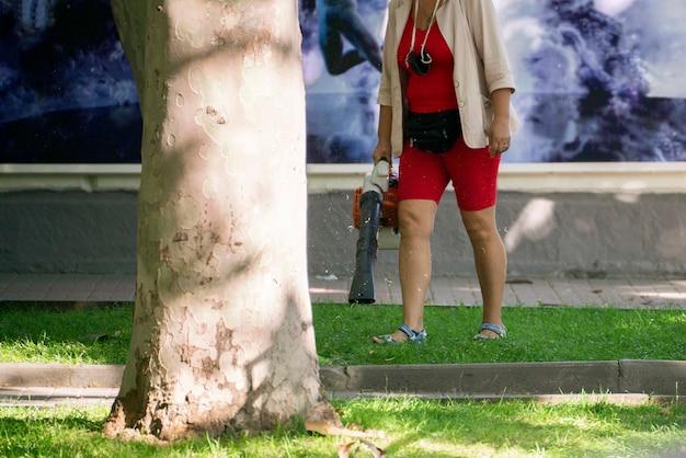 Eine person, die die stadtstraße mit einem staubsauger säubert, öffentlicher reinigungsdienst