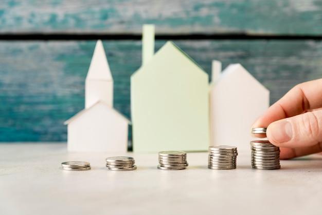 Eine person, die die zunehmenden münzen vor papierhäusern auf weißer oberfläche anordnet