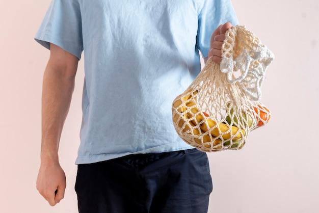 Eine person, die eine netztasche mit frischem rohkostobst und -gemüse hält, umweltfreundliches zero-waste-gespräch