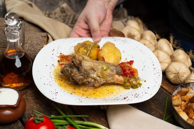 Eine person, die fleischeintopf mit kartoffeln und öliger suppe in der weißen platte in den händen hält.