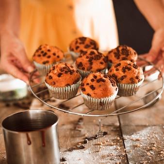 Eine person, die frische gebackene muffins auf abkühlendem behälter anhält