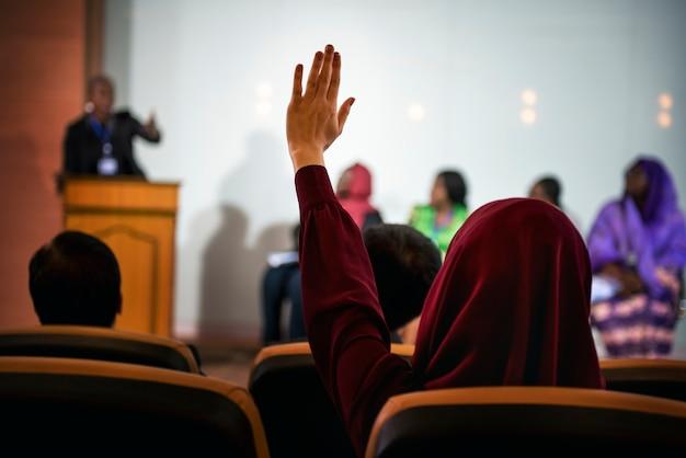 Eine person, die ihre hand erhebt, um eine frage in einer podiumsdiskussion zu stellen