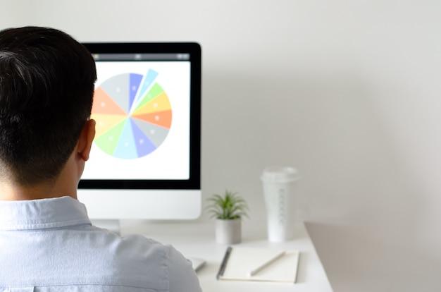Eine person, die im büro mit personal-computer-bildschirm arbeitet, die eine kaffee- und tillandsialuftanlage haben