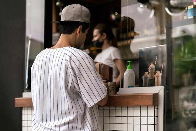 Eine person, die im straßencafé der stadt essen und kaffee kauft?