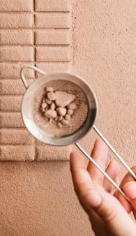Eine person, die kakaopulver vom sieb auf schokoriegel stäubt