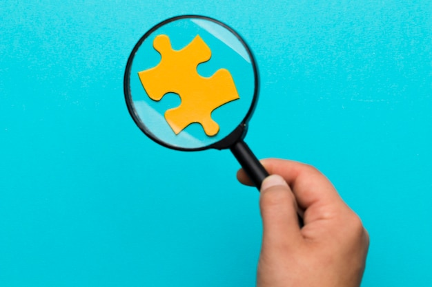 Eine person, die lupe über dem gelben puzzlespiel gegen blauen hintergrund hält