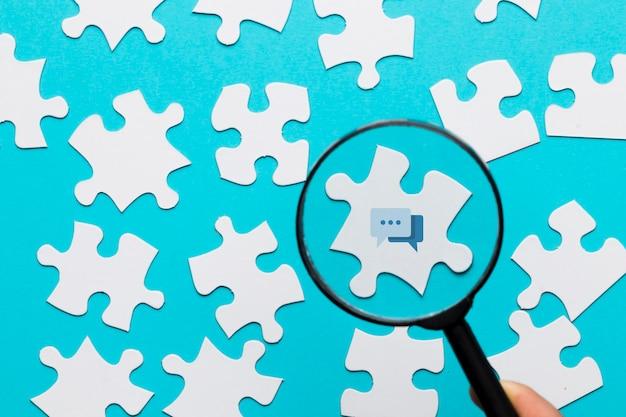 Eine person, die lupe über der mitteilungsikone auf weißem puzzlespiel gegen blauen hintergrund hält