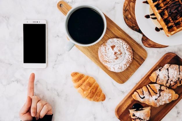 Eine person, die mit dem finger auf ein mobiltelefon und gebackene brötchen zeigt; croissant; waffeln und kaffeetasse auf dem schreibtisch