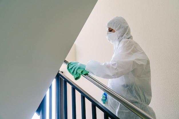 Eine person, die mit sicherheitskleidung vor einer pandemie oder einem virus geschützt ist, reinigt und desinfiziert ein portal eines hauses