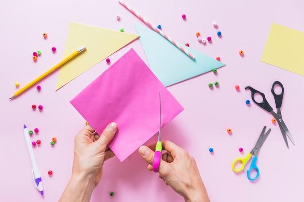 Eine person, die papier mit scissor über dem rosa hintergrund schneidet