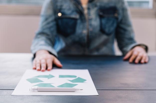Eine person, die recyclingpapier mit stift auf holztisch zeigt