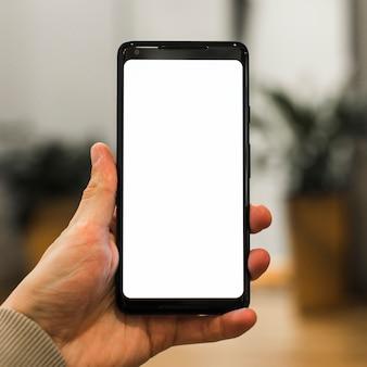 Eine person, die sein neues smartphone vor unscharfem hintergrund bewirbt