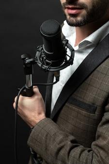 Eine person, die stehendes mikrofon hält