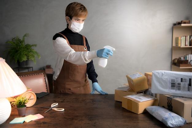 Eine person, die während der coronavirus-covid-19-pandemie desinfektionsmittel auf pakete und kartons sprüht