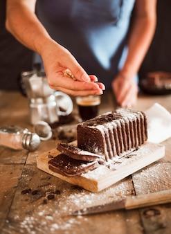 Eine person, die walnussstreichungen über der scheibe des kuchens auf hackendem brett gibt