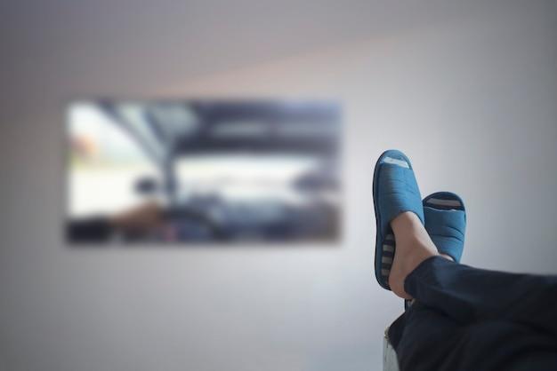 Eine person, die zu hause liegt und fernsehen, beine auf den tisch legen, genießen und entspannen