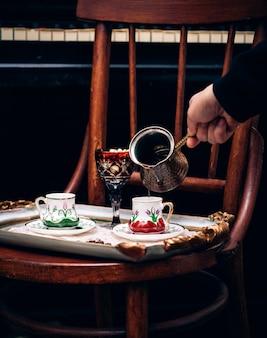 Eine person gießt kaffee in eine tasse