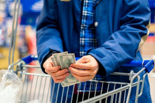 Eine person in einem lebensmittelgeschäft, hände zählen die geldwährung