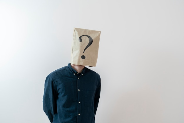 Eine person mit einer papiertüte auf dem kopf mit fragezeichen, zeichensymbol des problems